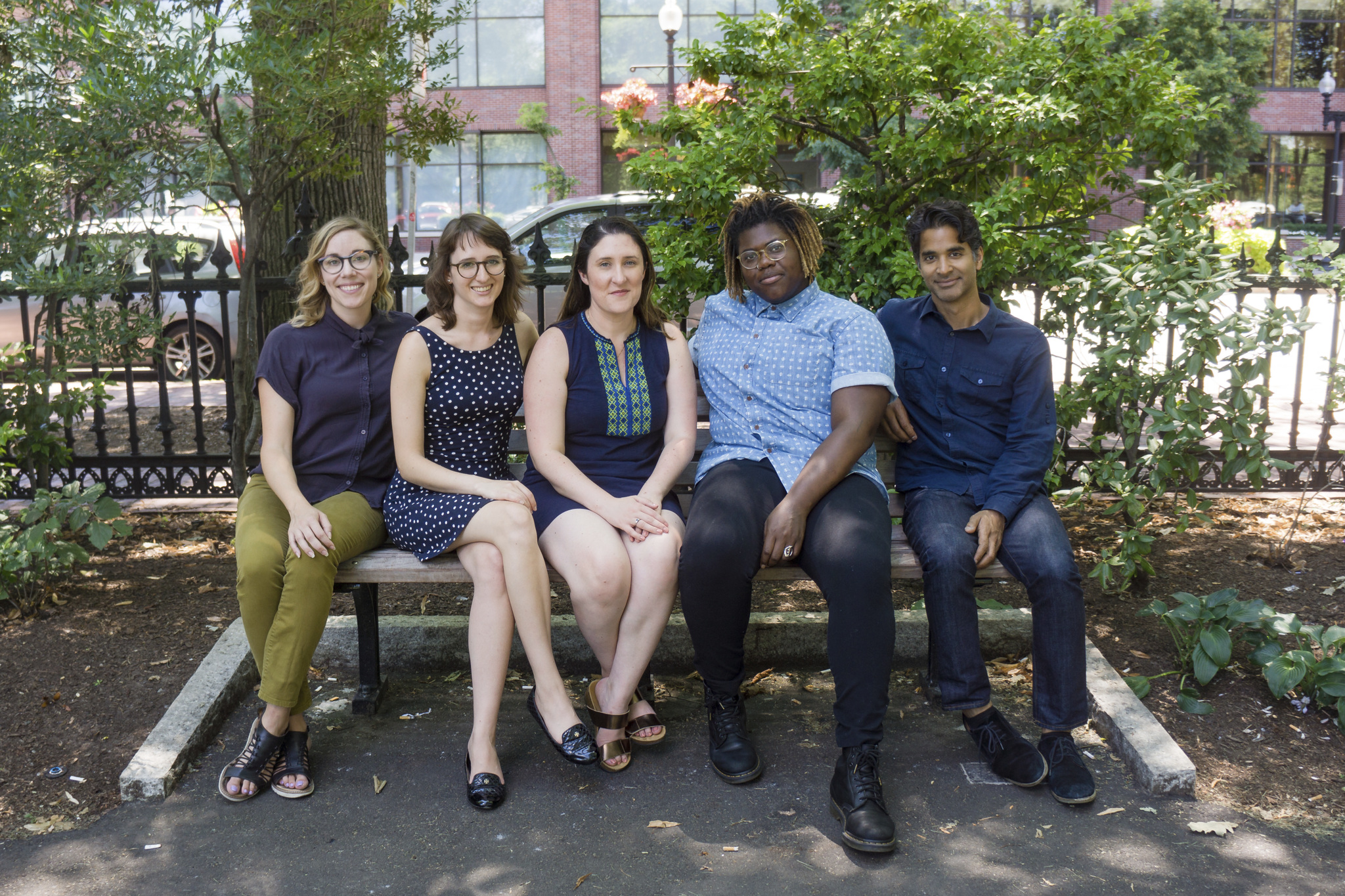 Five HowlRound staff members sit on a bench.