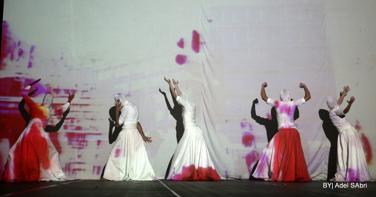 five performers in white dance against a wall with projection