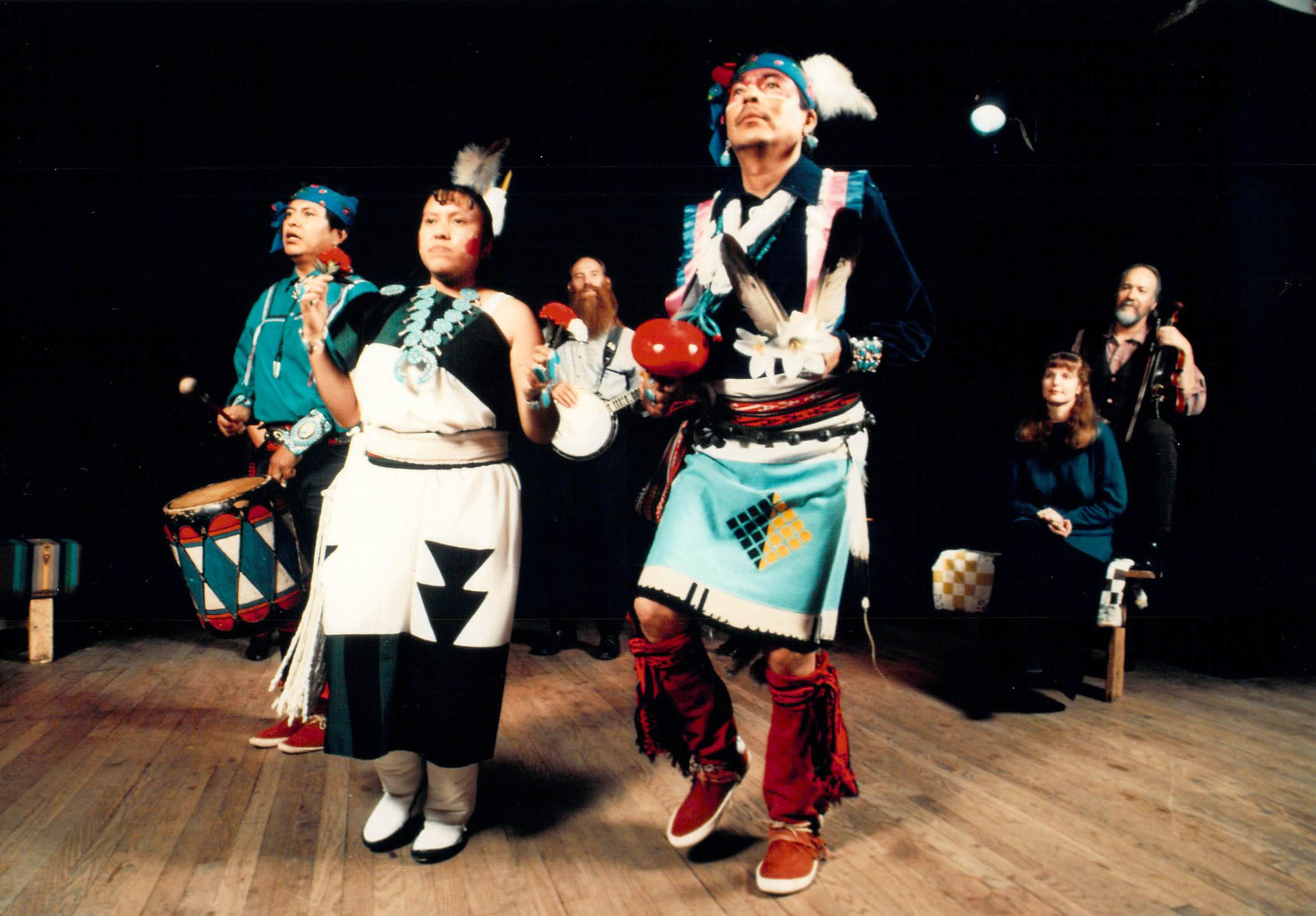 three performers in traditional Native American costume