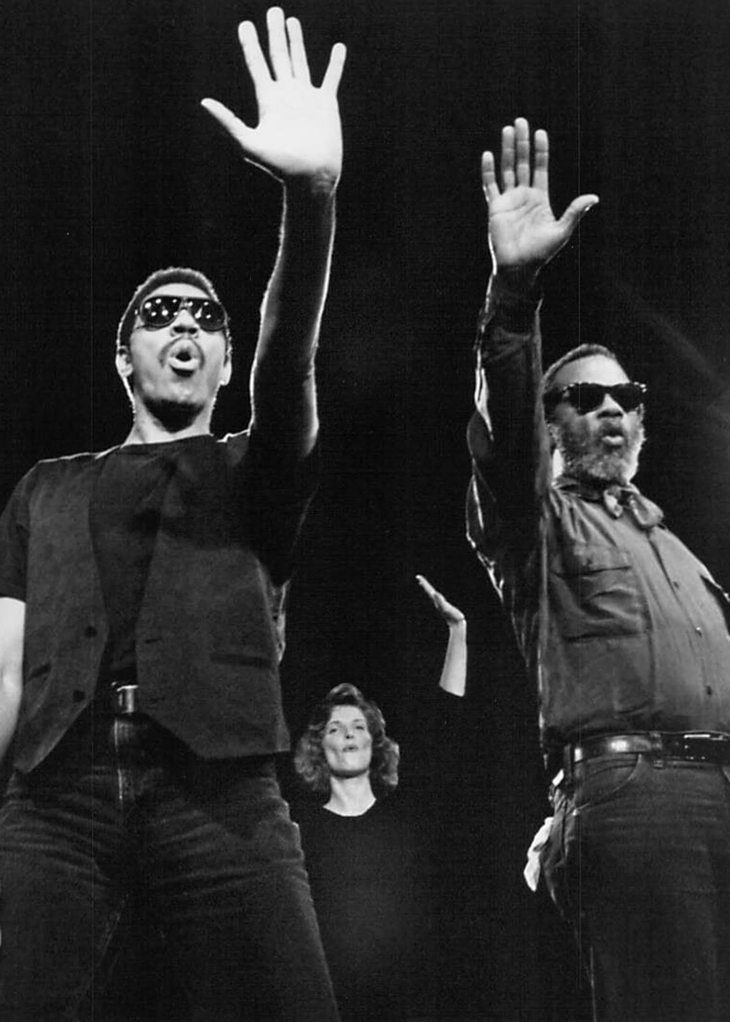 three performers wearing sunglasses with outstretched hands