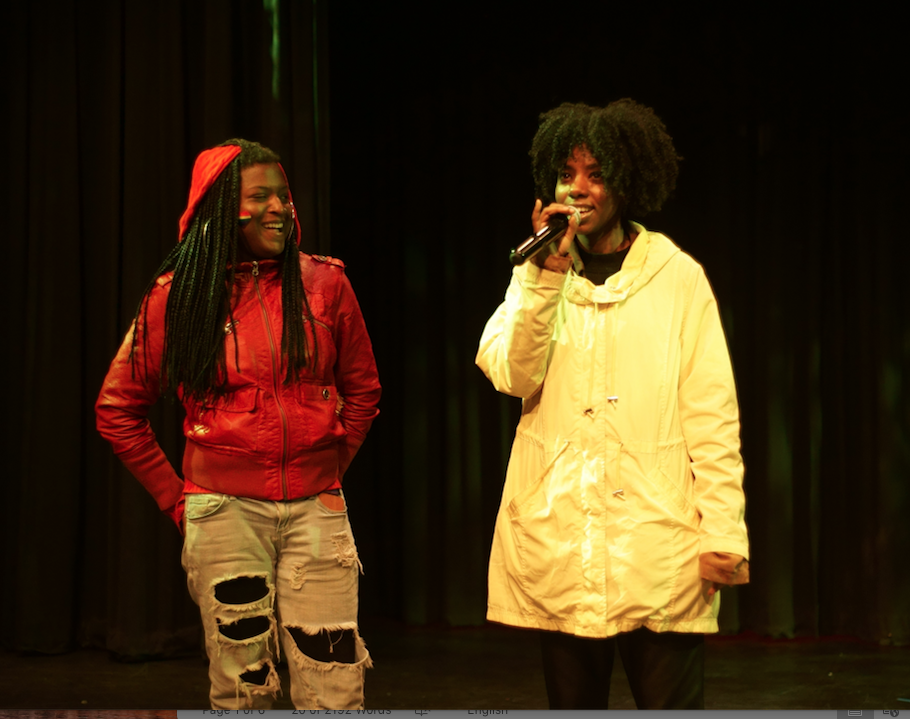 two performers smiling onstage, one holding a mic