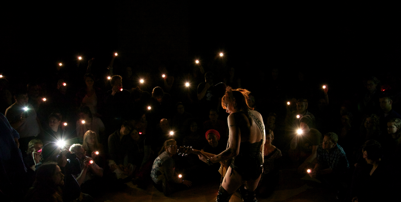 silhouette of performer playing guitar to a crowd of people holding flashlights