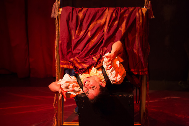 An actor in period costume hangs upside down in a frame on stage.