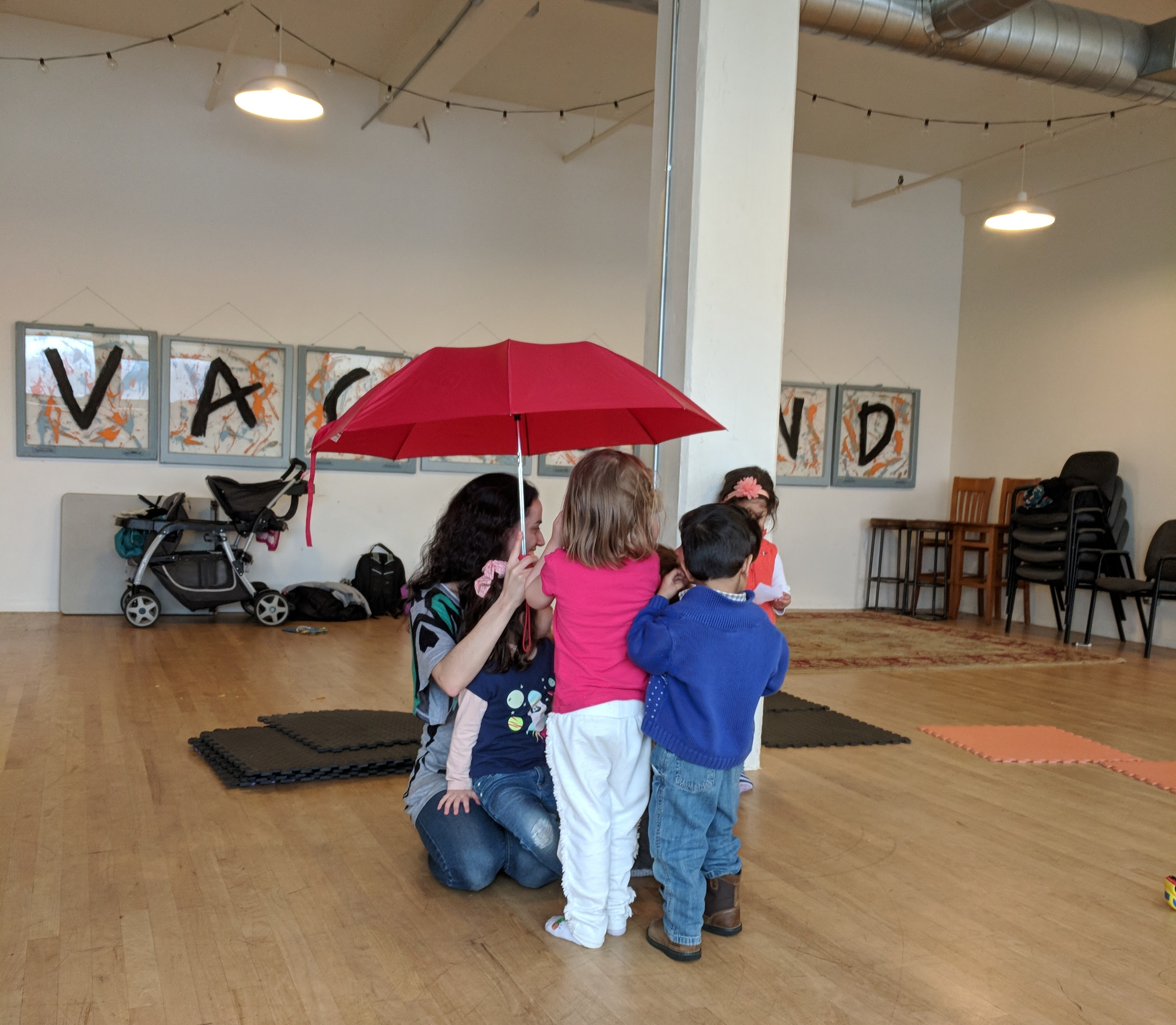 children standing under an umbrella