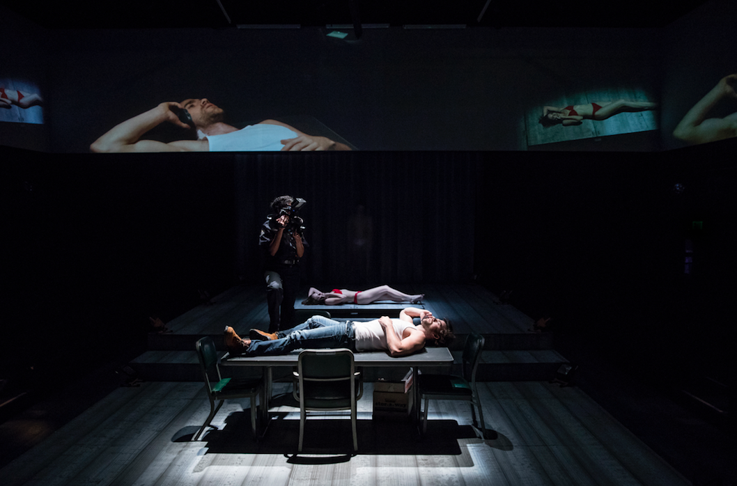 person lying down onstage, surrounded by screens.