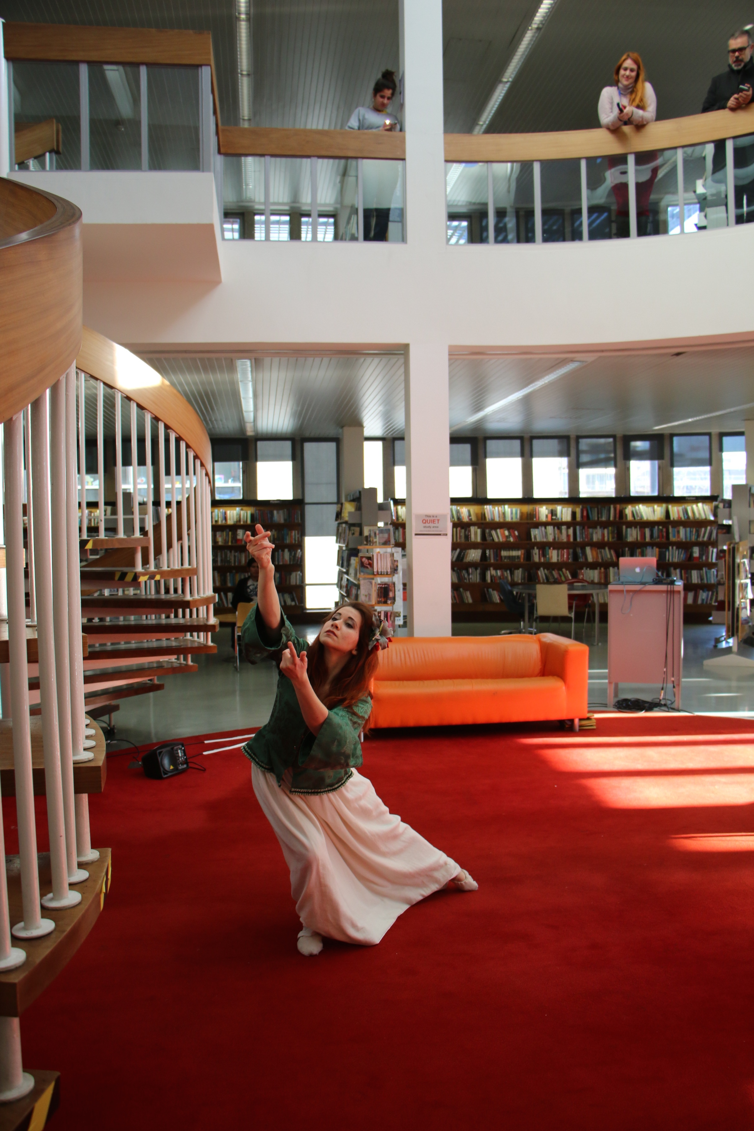 performer dances in a library while audience members watch
