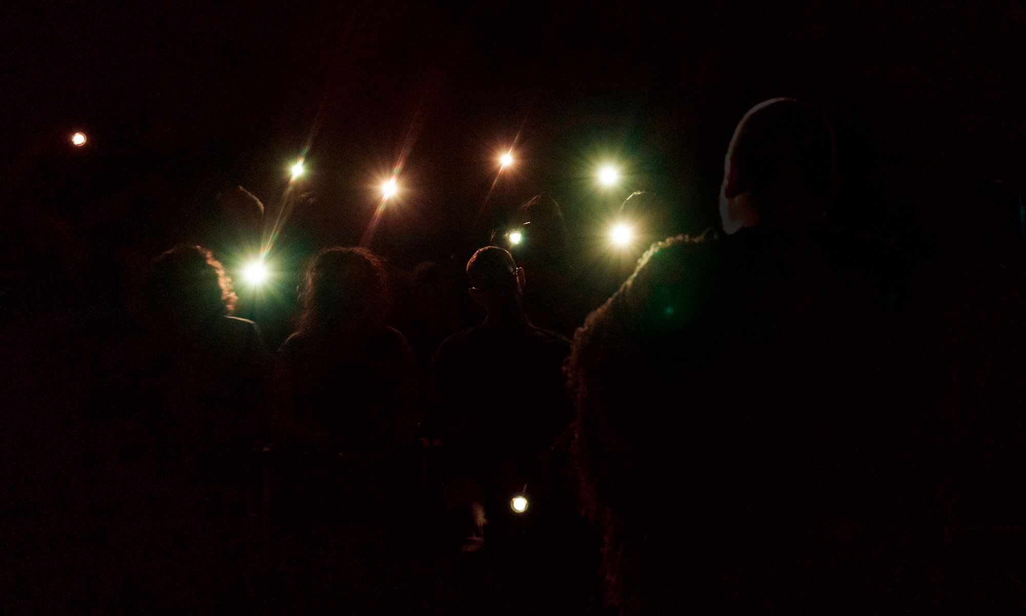 audience in darkness, except for flashlights