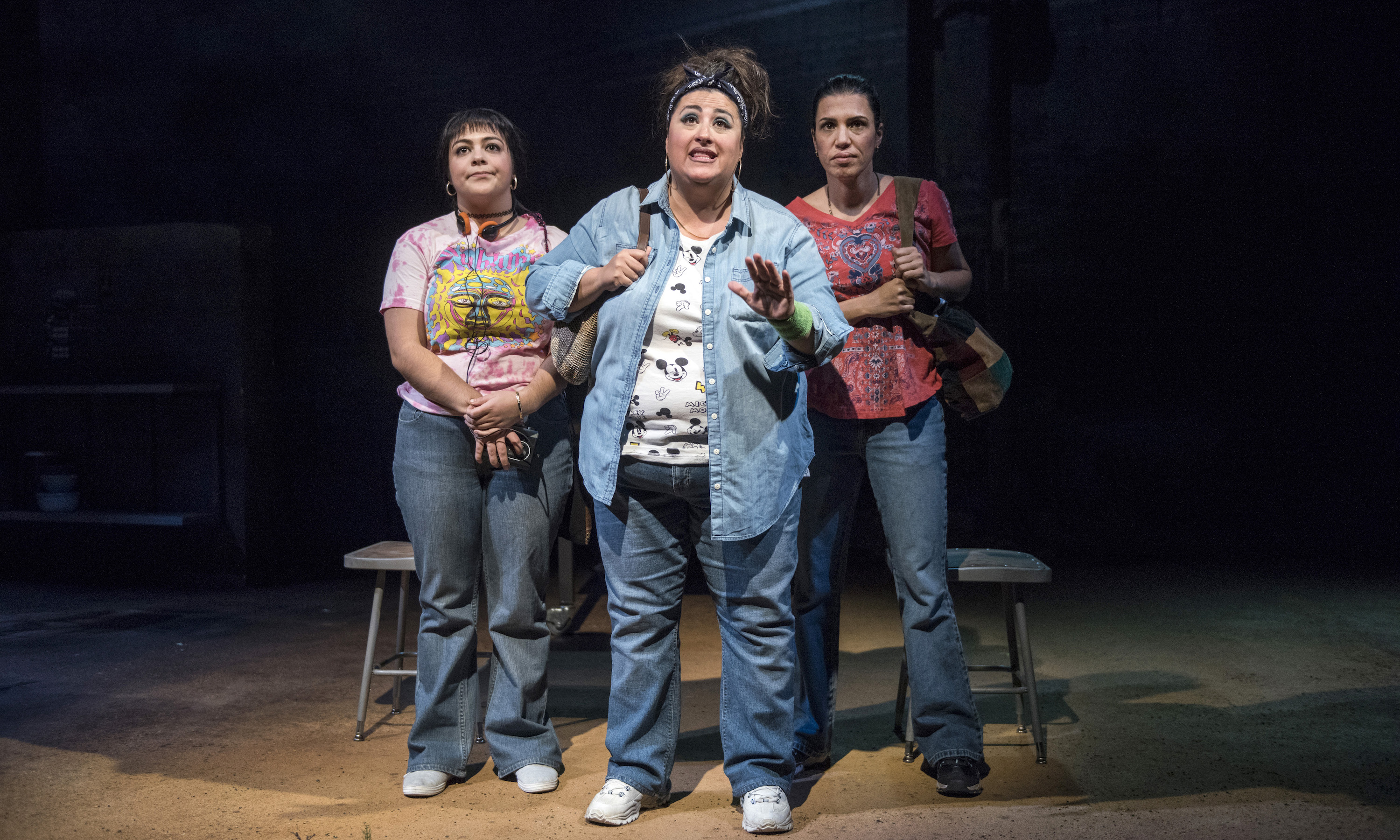 Three women huddled on stage
