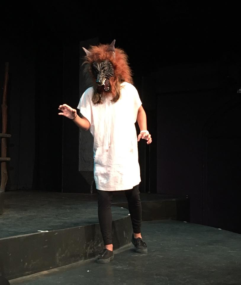 Actor on stage wearing a wolf mask