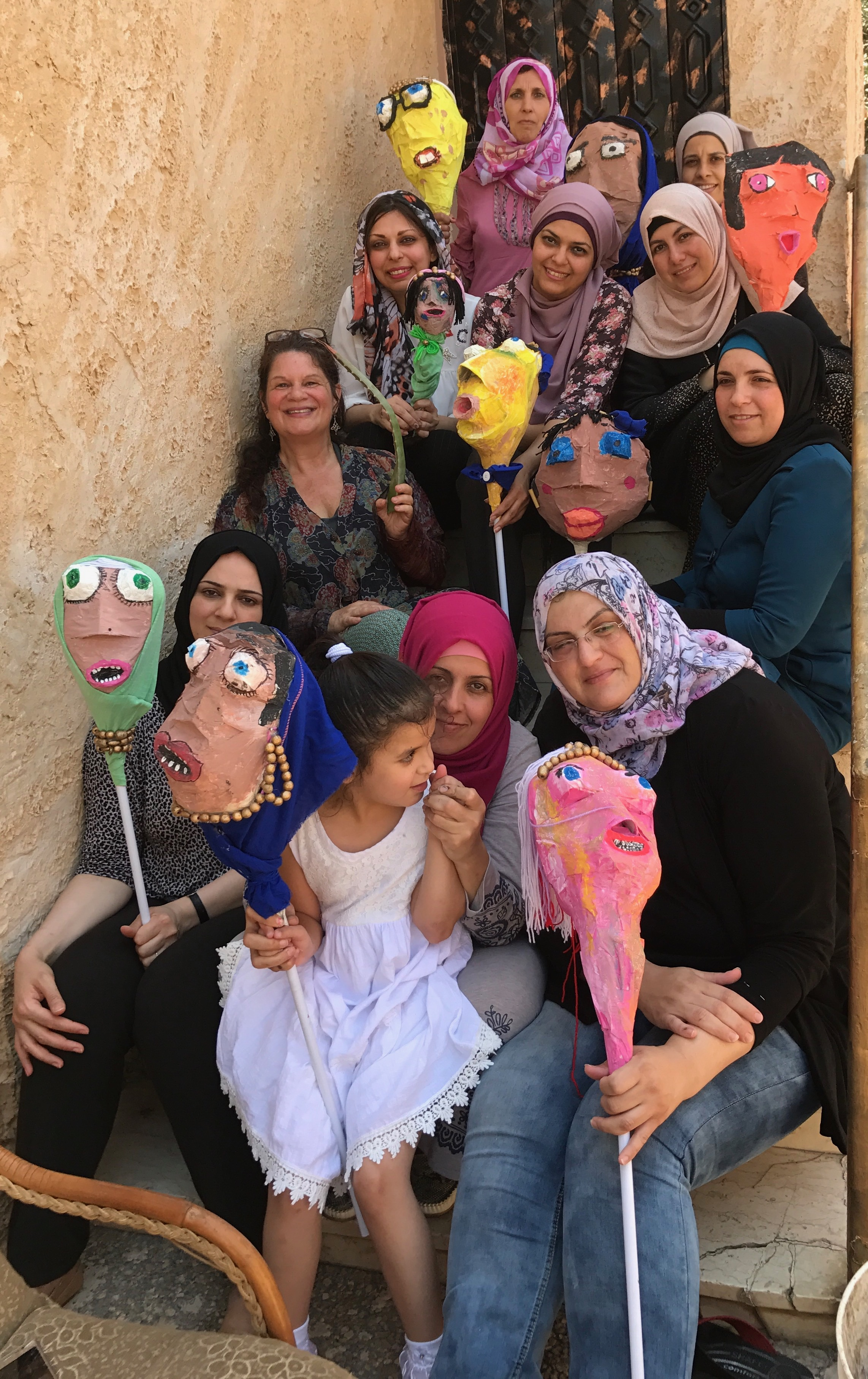 a group of smiling people holding puppets