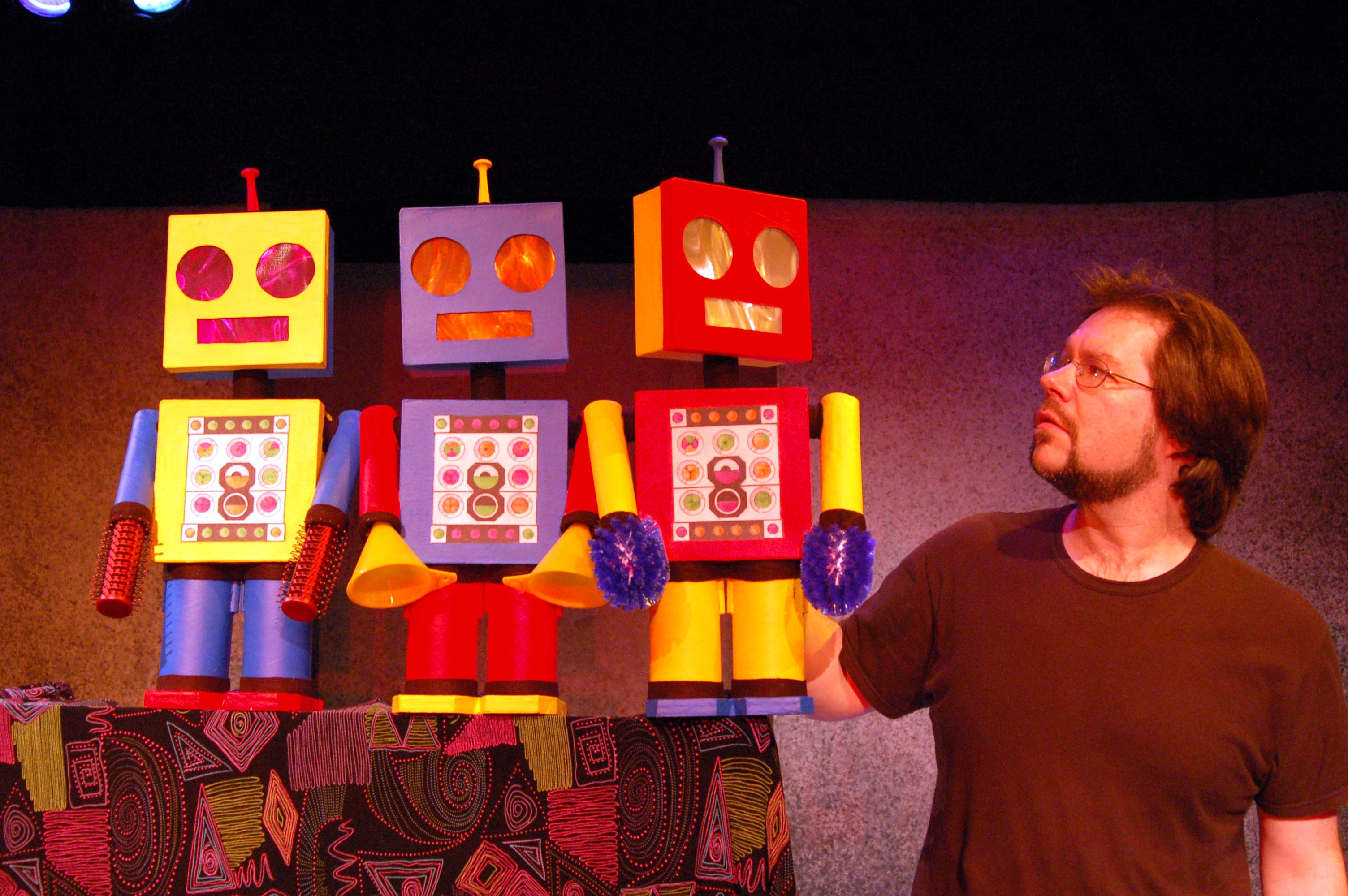 an actor onstage with three robot props