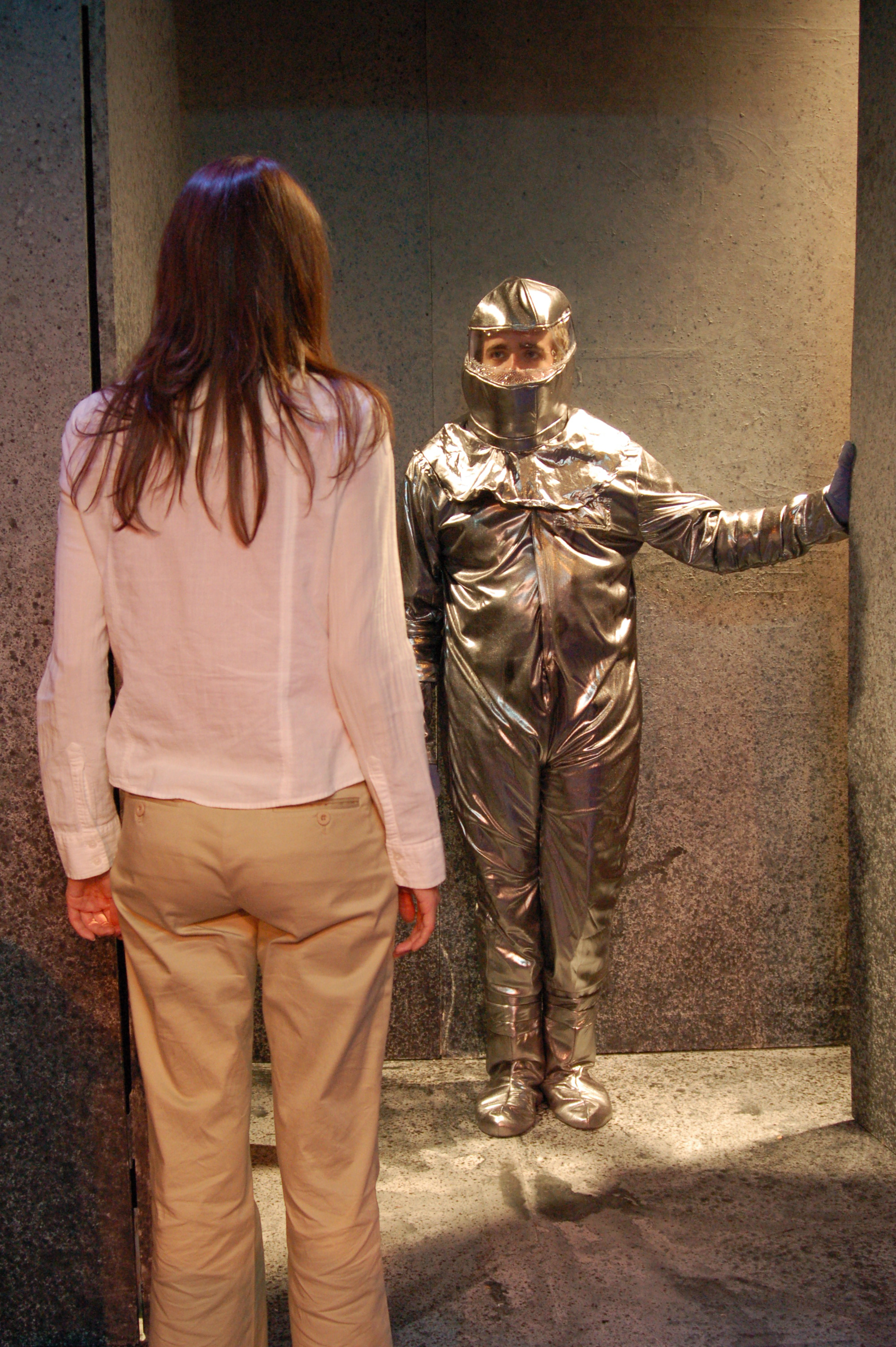 two actors stand towards each other, one in a silver suit