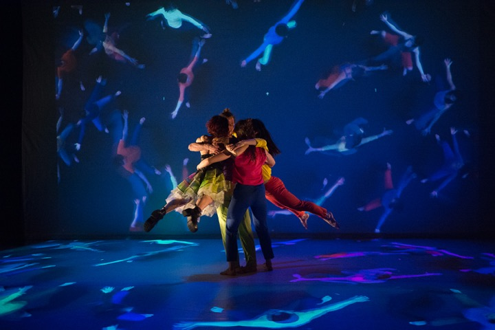 two dancers embrace around projection