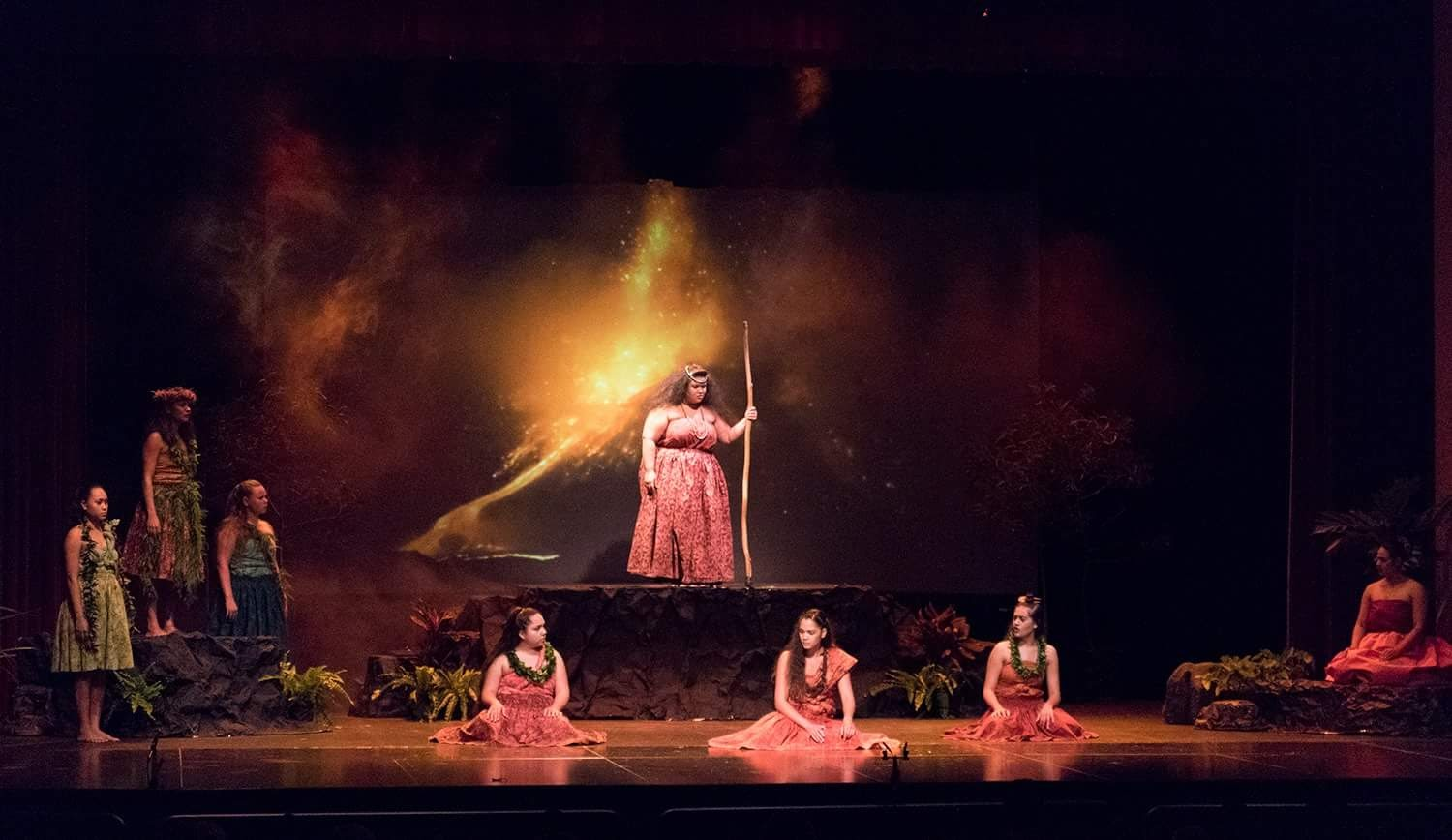 Perfomers on stage in front of a volcano