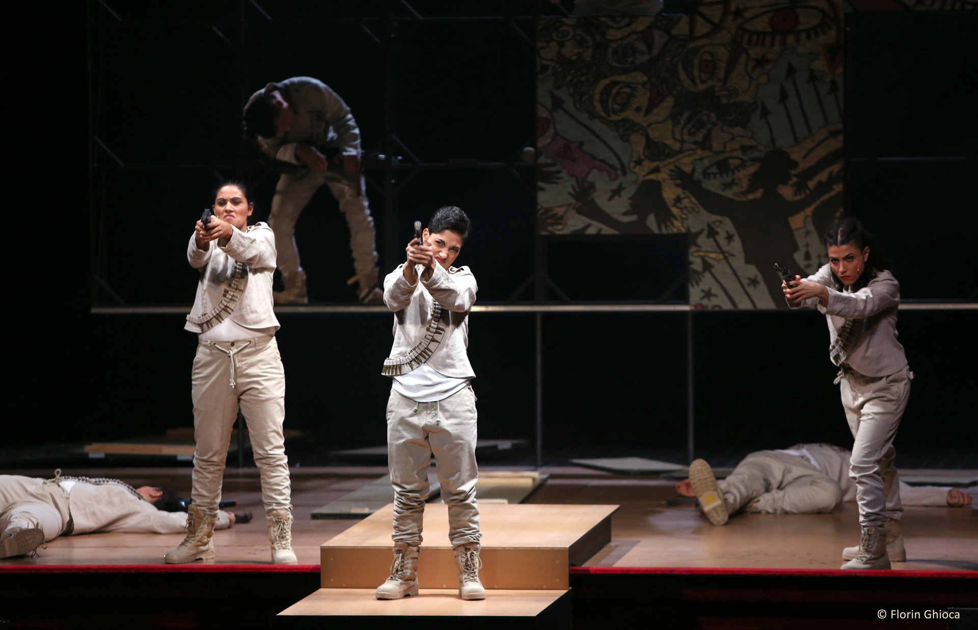 three performers holding guns onstage