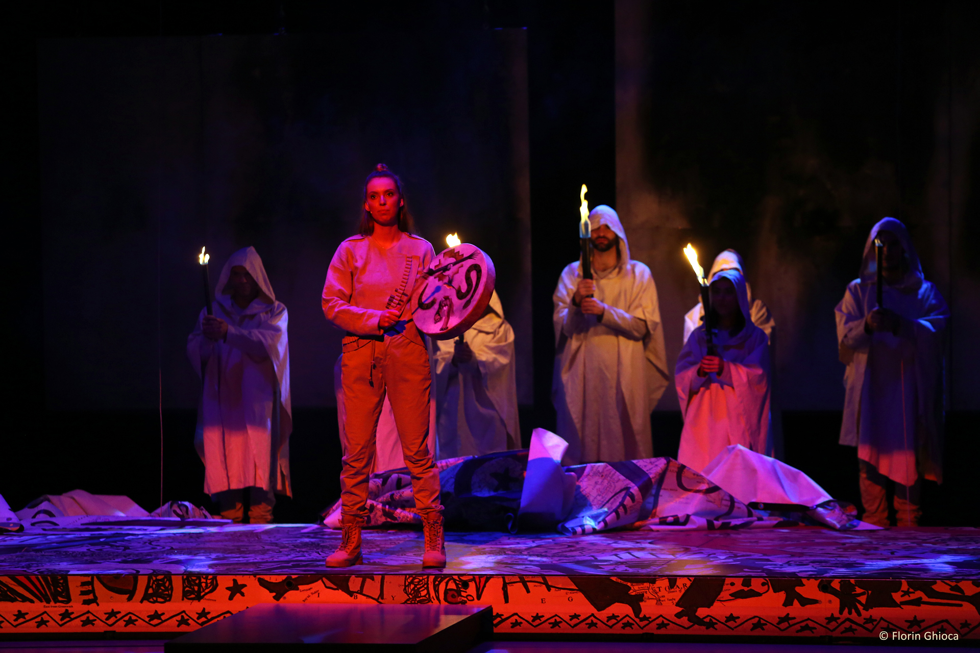 performers onstage in hoods holding torches, one person standing and holding a drum