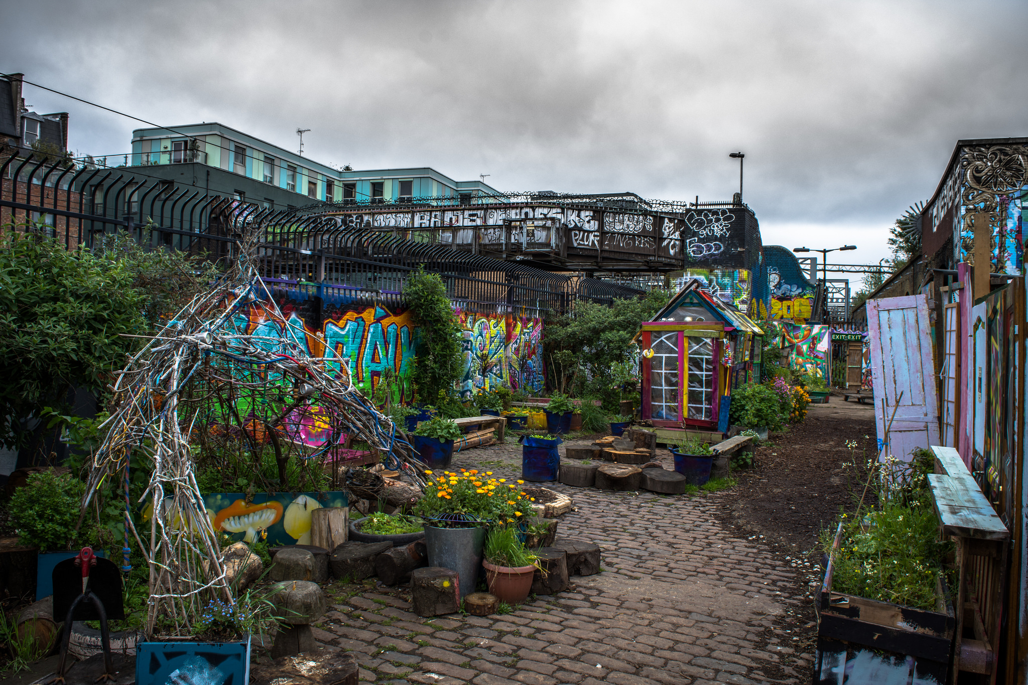 colorful community garden with graffiti on brick walls