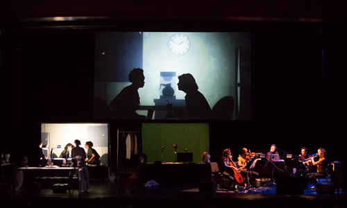 actors and musicians onstage underneath a projection