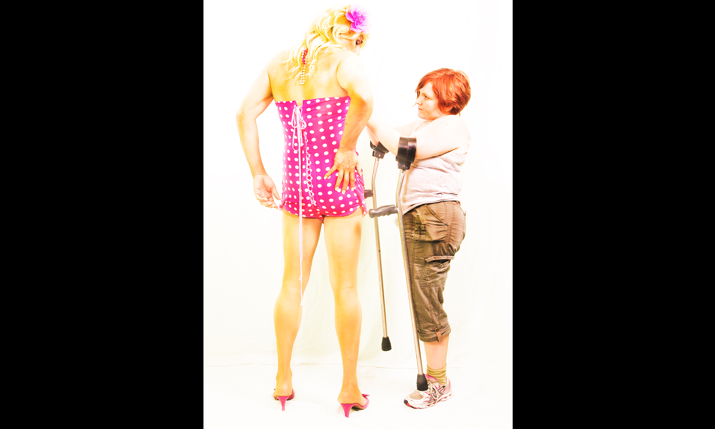 T-girl in pink polkadot top swimsuit with blond wig and kitten pumps, Mallory standing with arms up and crutches hanging, putting finishing touches on