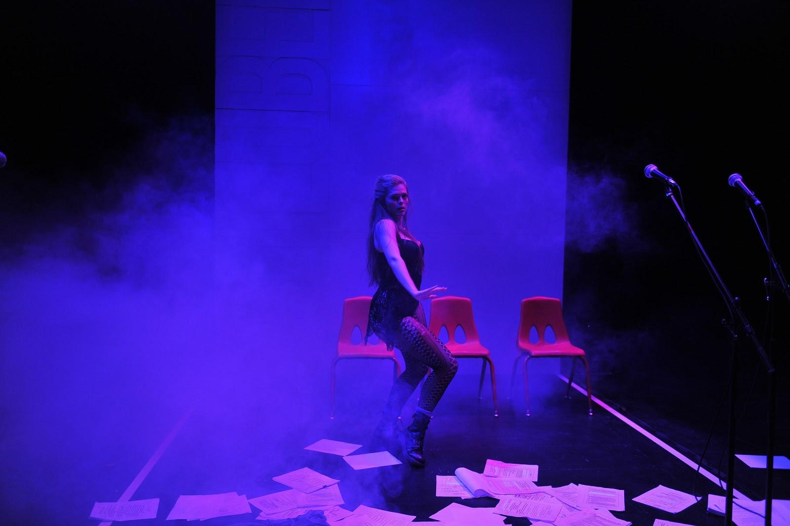 performer in foggy blue light dancing in front of chairs