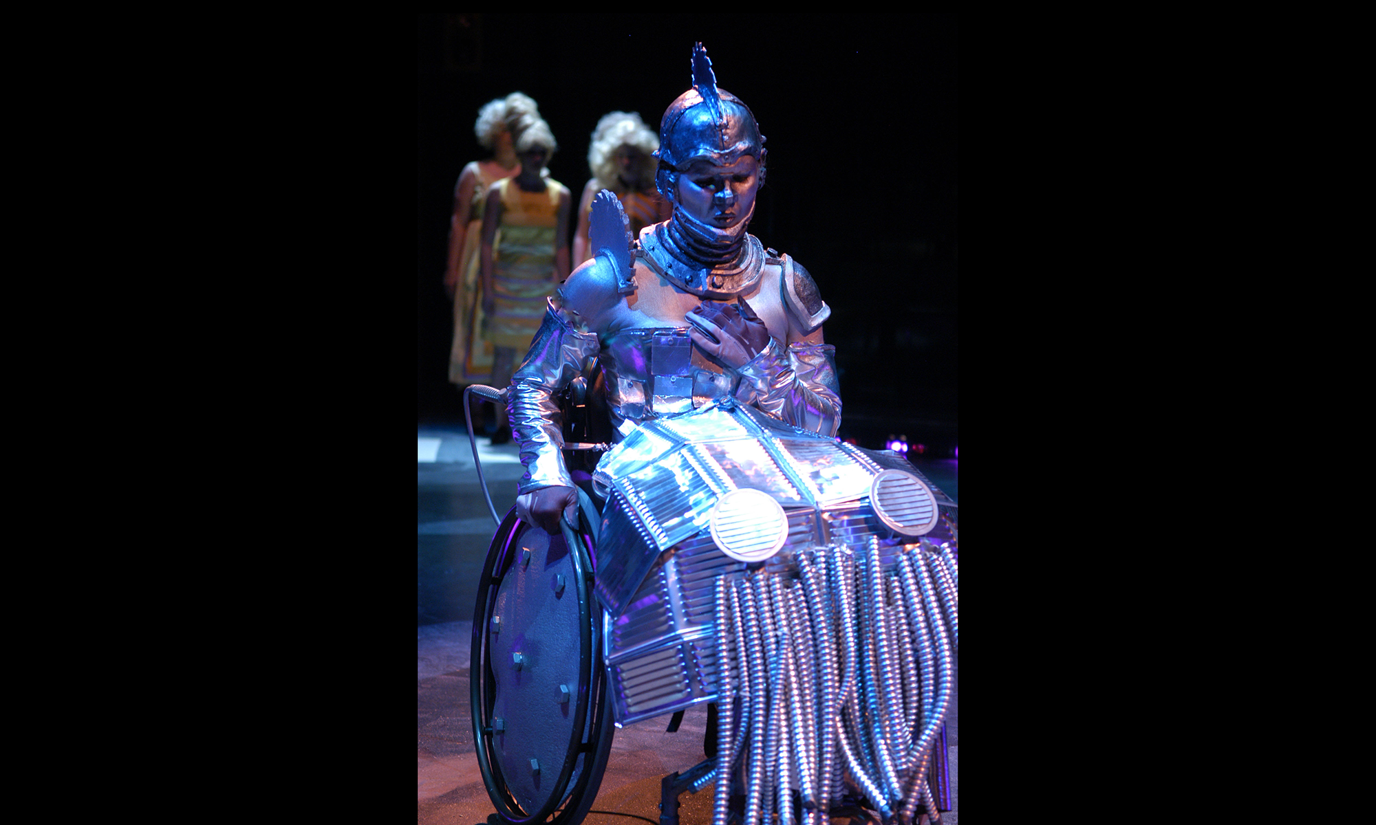 wheelchair user in dramatic lighting in tin metal costume from head to wheel, saw blade on top of head and shoulders, metal-plated corset and metal skirt