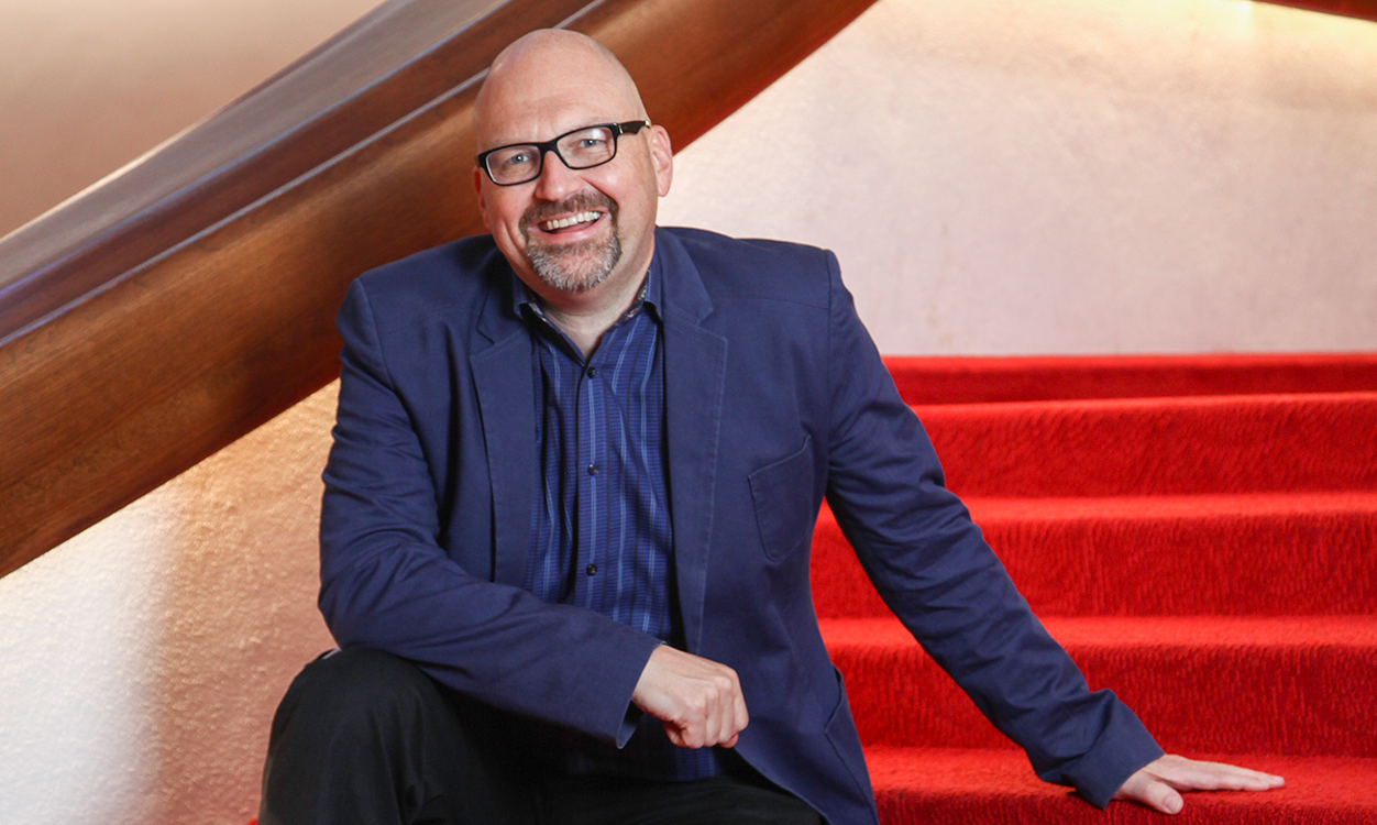 a bald man with glasses and a beard in a navy suit sitting on red stairs