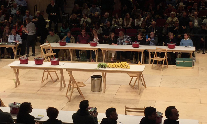 two audiences looking on a stage at two tables with food and pots on them