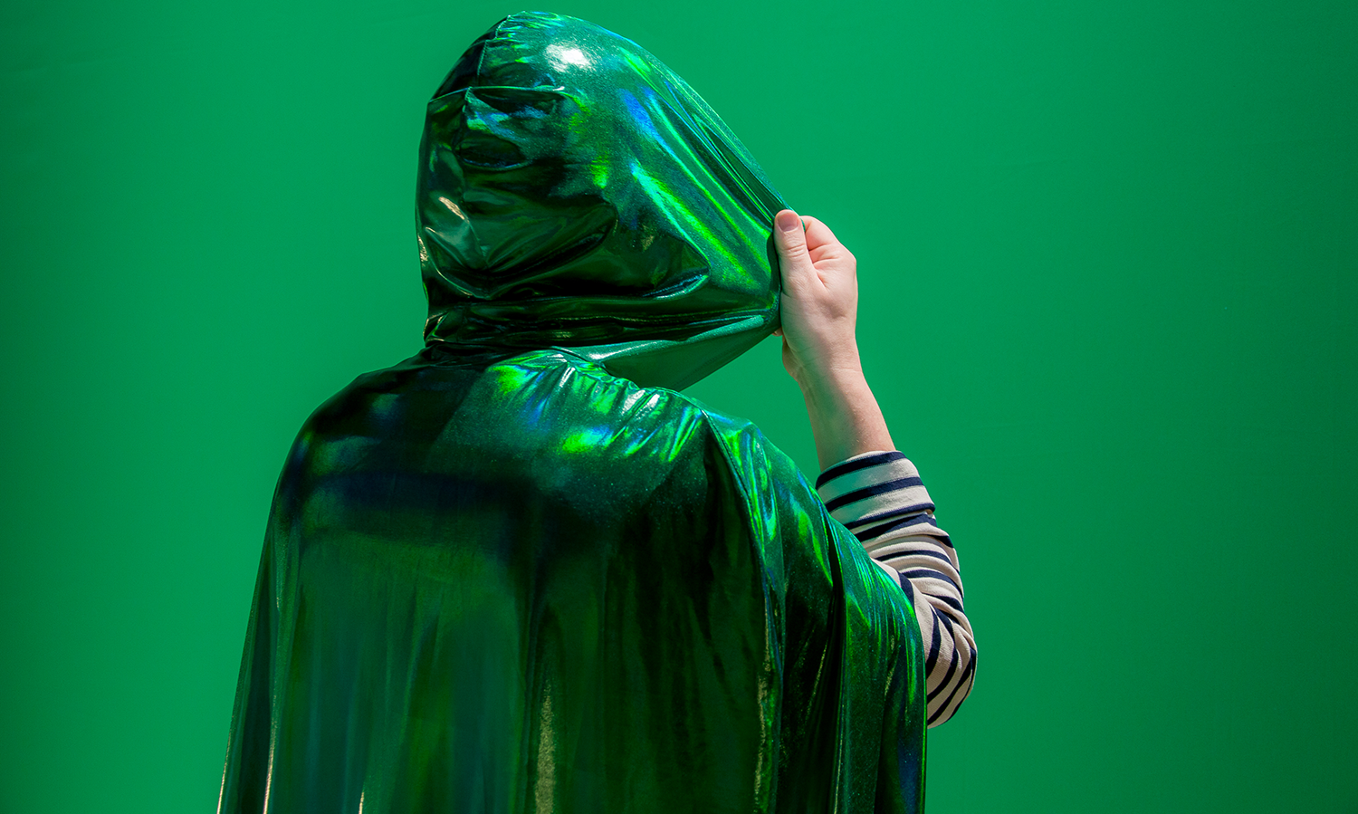 a hooded figure in green against a green background