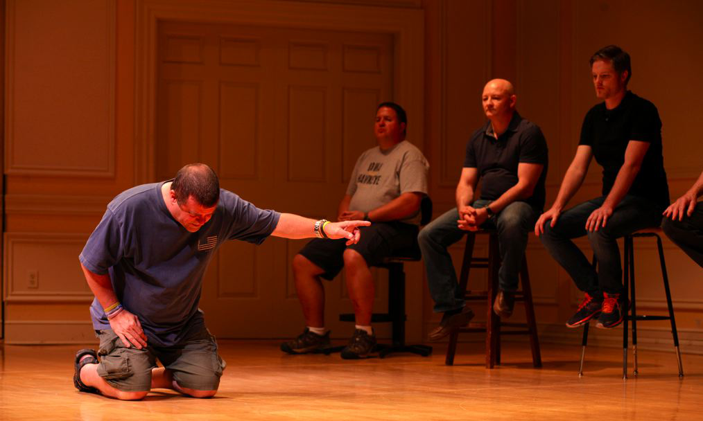 an actor kneeling onstage before four seated actors
