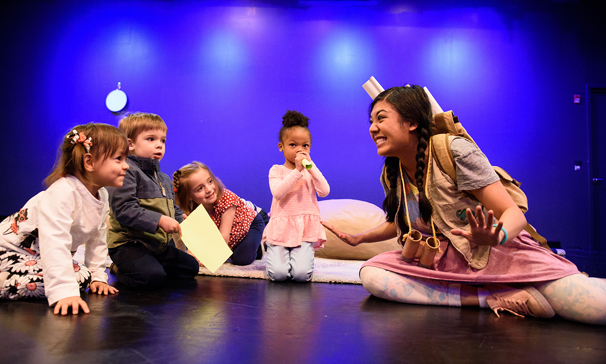an actor onstage with four young children