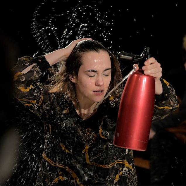 woman performer spraying herself with a seltzer water can.