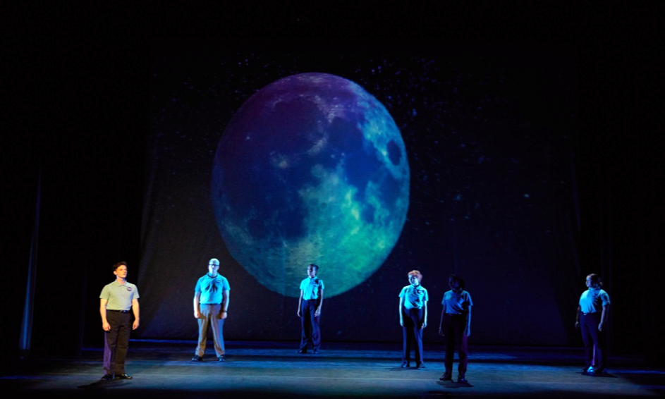 six actors onstage under a projection of the full moon