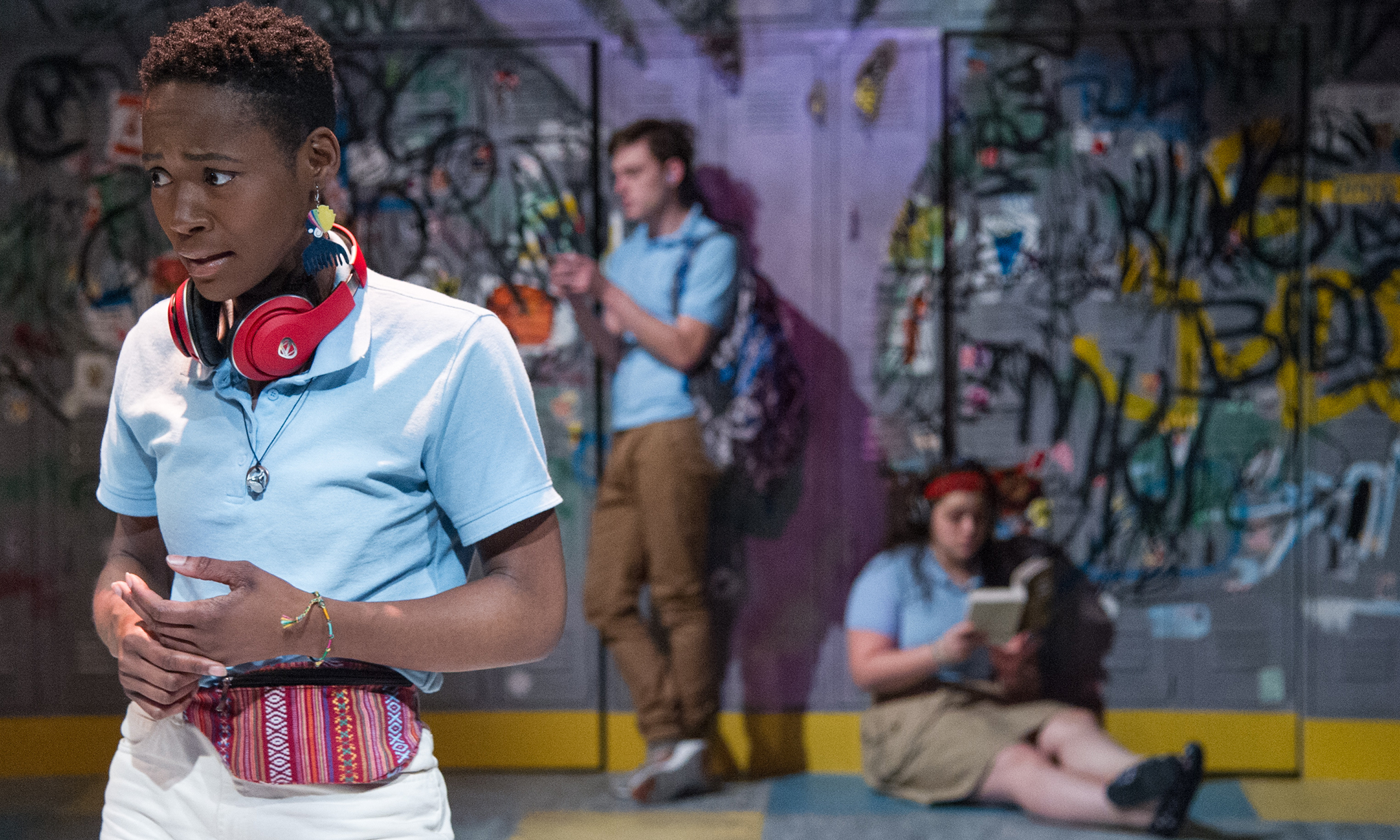 Three young actors in school uniforms onstage in front of a graffiti wall.