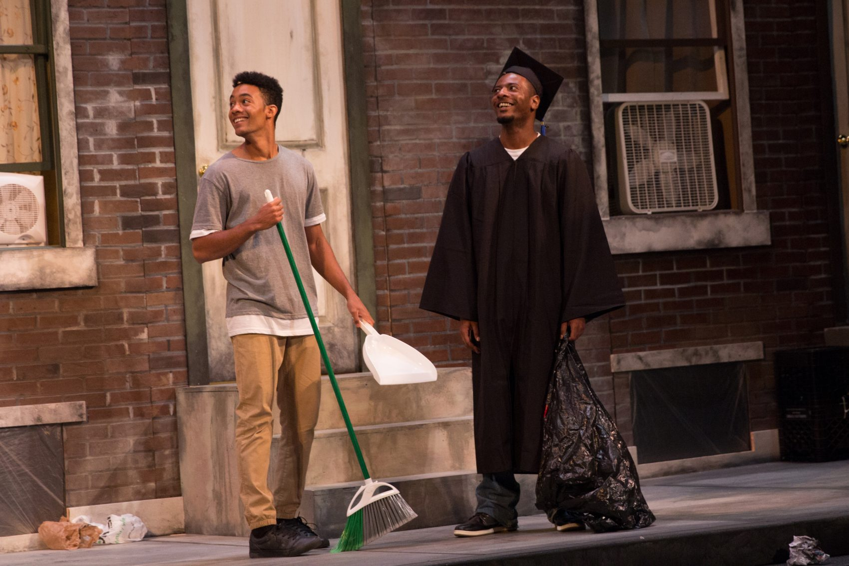 two actors on a porch, one holding a broom, and the other in a cap and gown holding a trash bag.