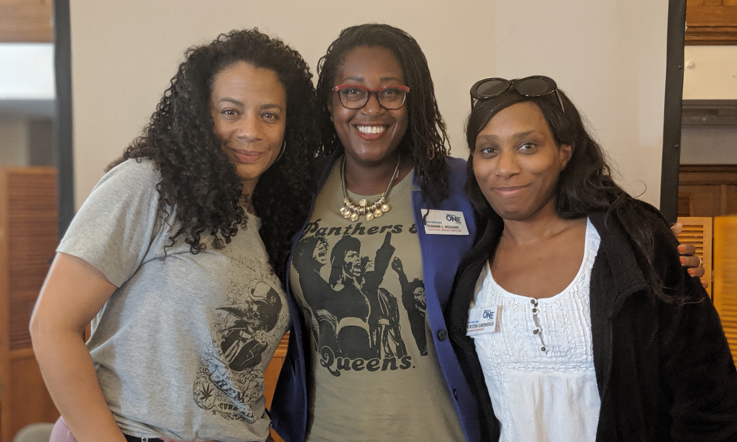 three Black woman smiling at the camera.