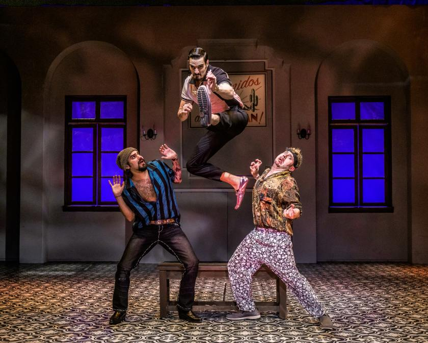 three actors onstage, one jumping up in the air.