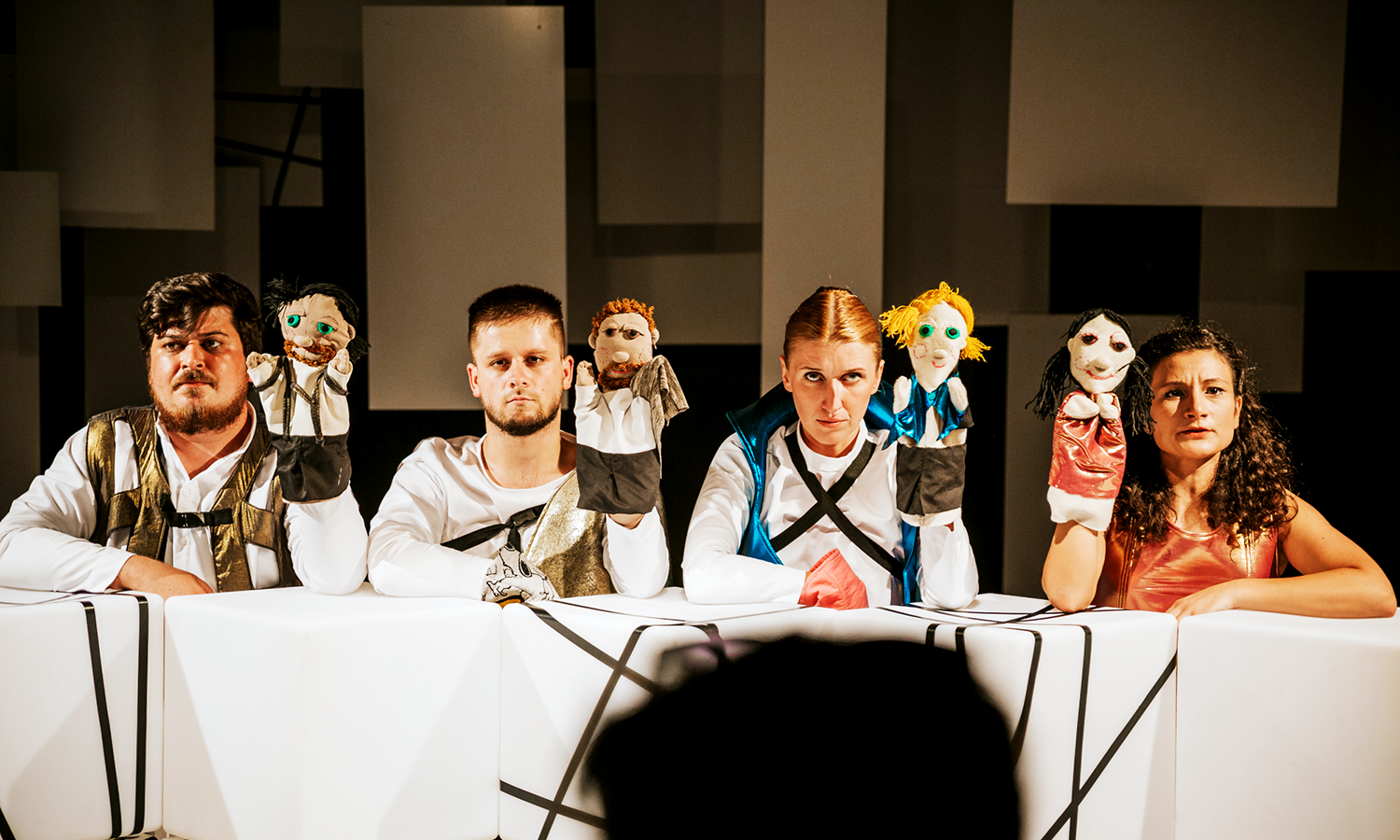 four actors with hand puppets onstage