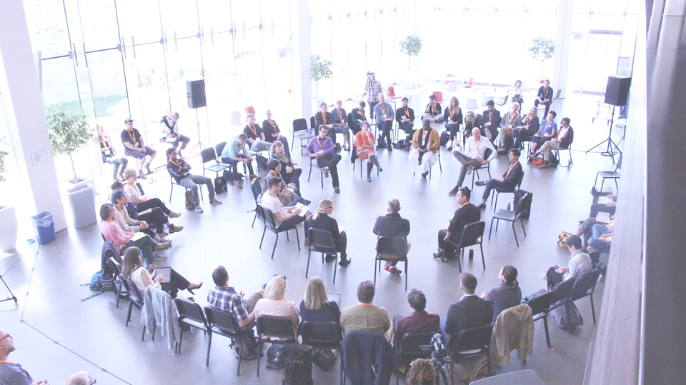 balcony view of a large group sitting in concentric circles