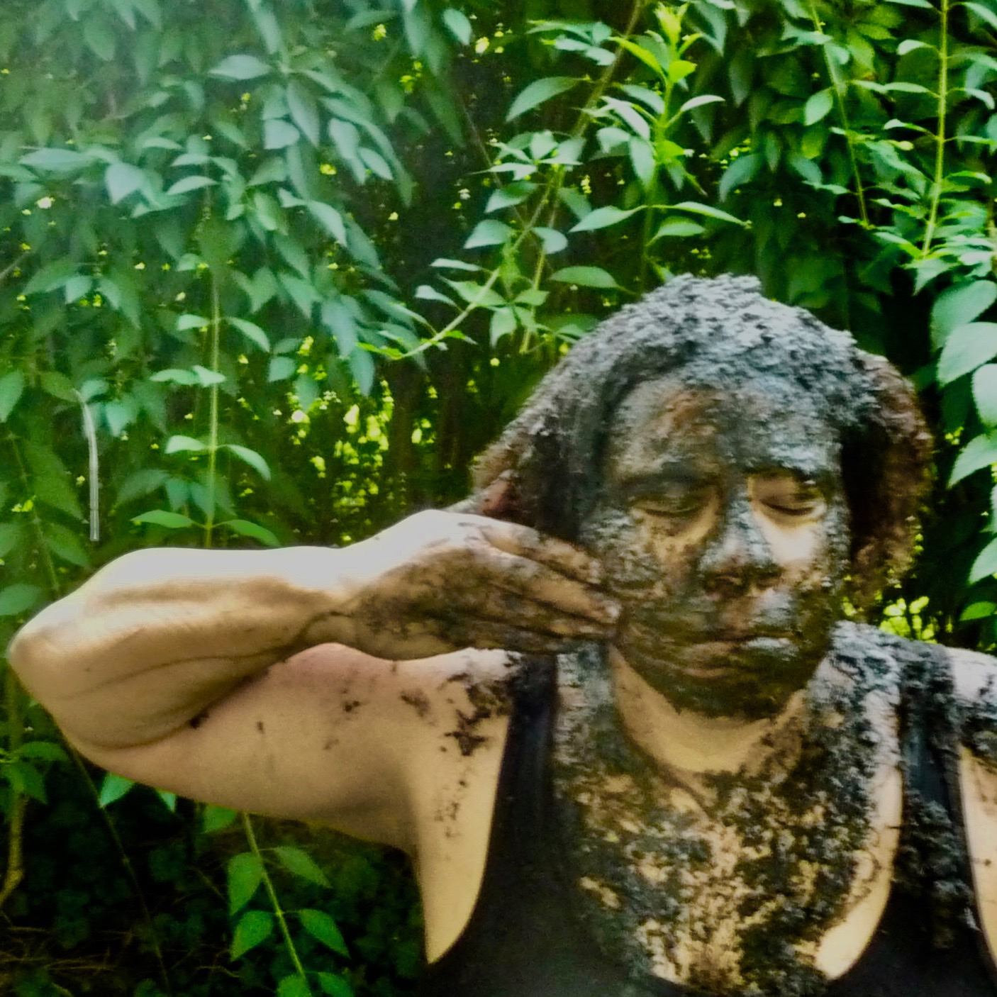 A woman of color smearing mud on her face