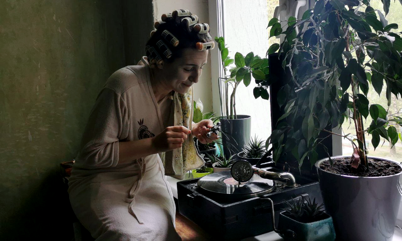a person in curlers and a robe seated in front of a record player and plants