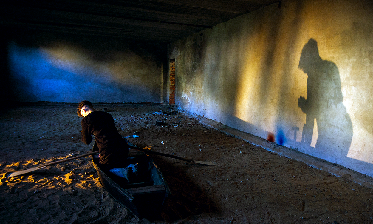 a person crouching in a boat in a large, empty room with concrete walls and dirt floor. their shadow is on the wall to their right