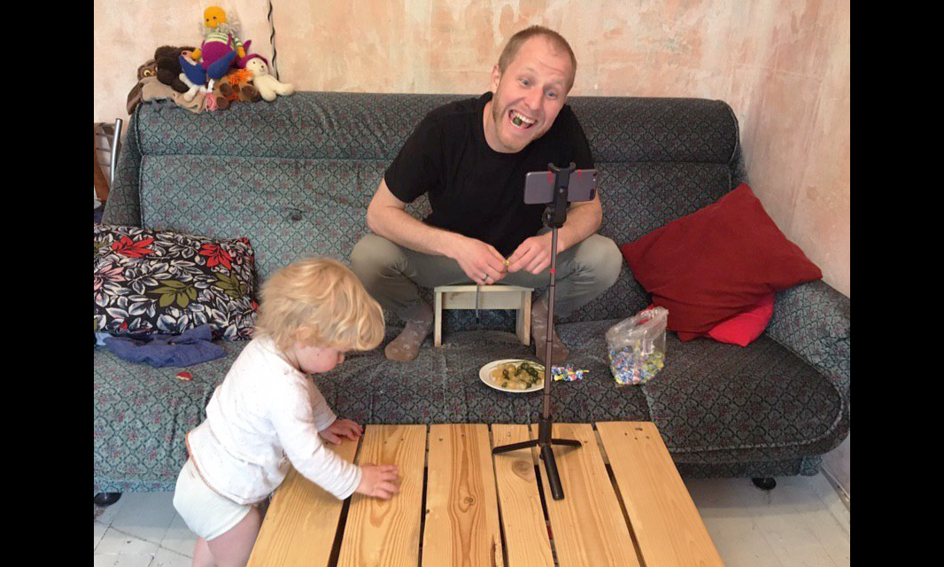 a person seated on a couch recording themselves on a phone situated in a stand on a coffee table. their child is to their right with their hands on the table