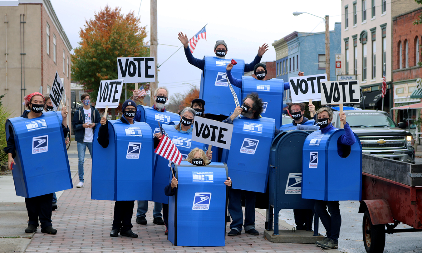 a group dressed as blue US mailboxes posing for a photo