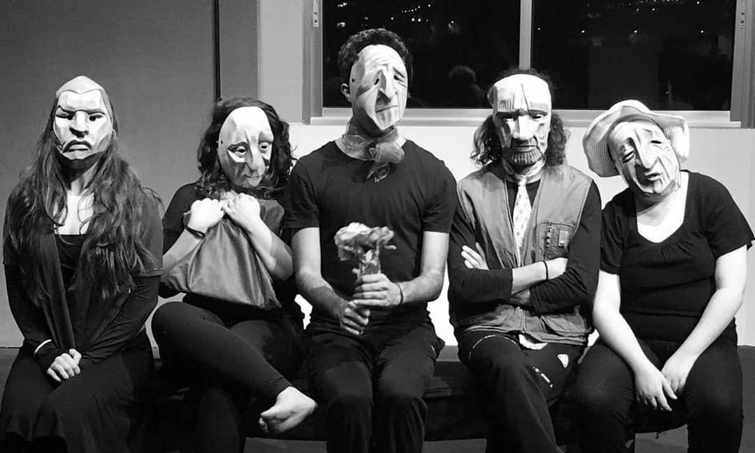 black and white photo of five seated people in masks
