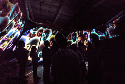 an audience in a room filled with large projections