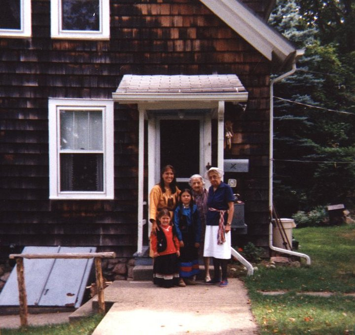 Five people stand in front of a house