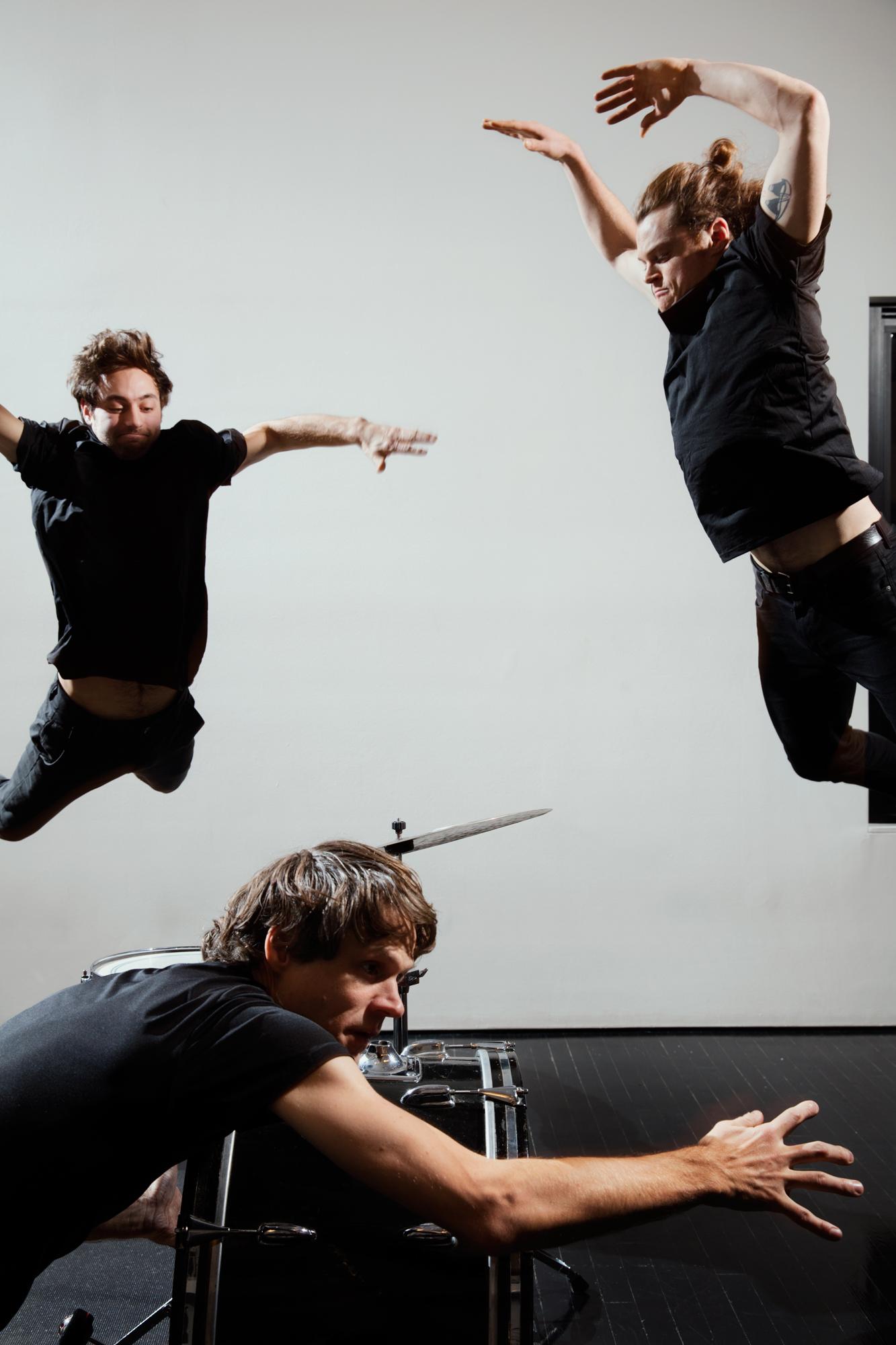 three men dancing around a drum