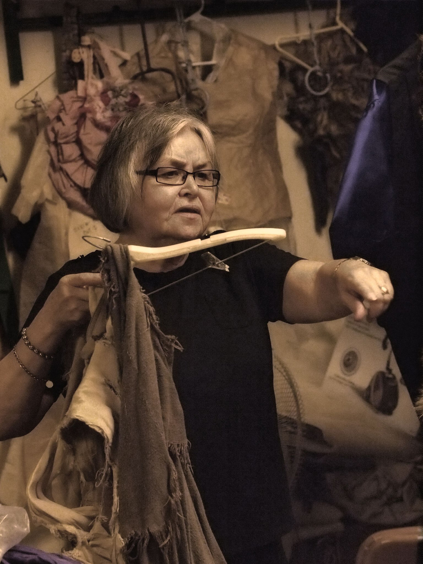 a woman on stage holding a hanger