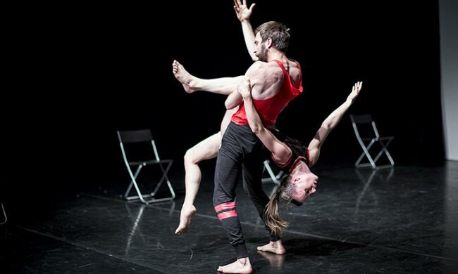 Two people holding each other in acrobatic dance.
