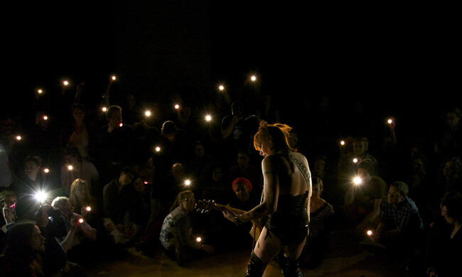 silhouette of performer playing guitar while audience watches, holding flashlights